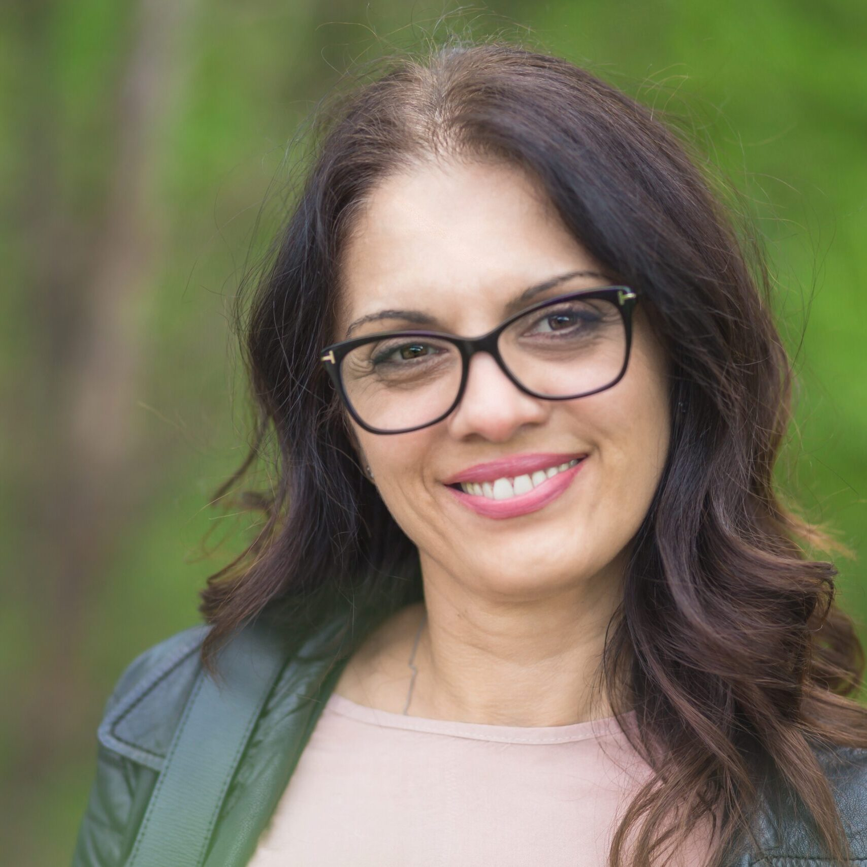 Beautiful, powerful middle-age brunette woman with glasses smiling. Springtime, outdoors
